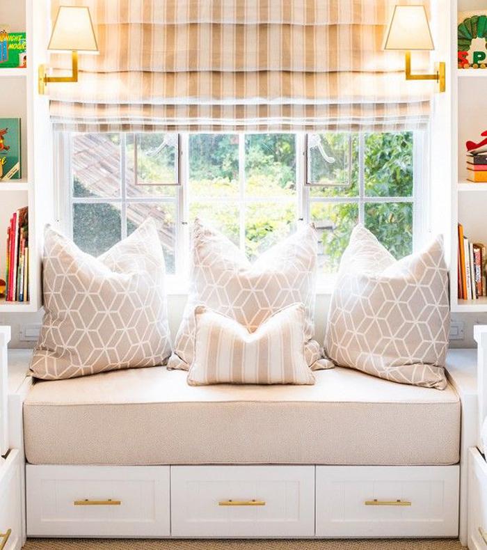 Asiento bajo ventana con una colchoneta alta y cojines